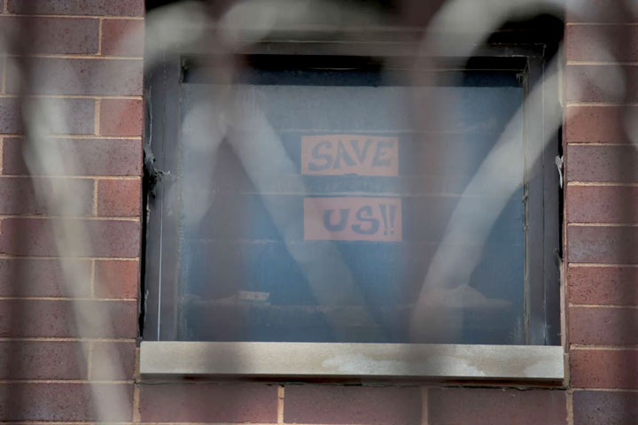 Save Us sign on the window of a US prison cell